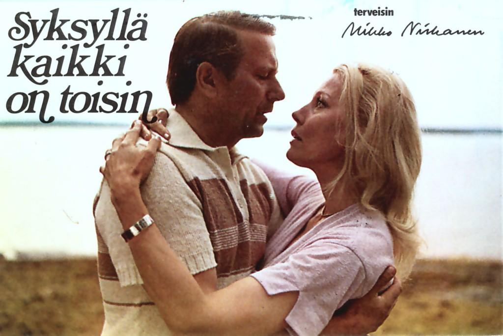"""Nyt helmikuussa kuollut Tea Ista oli naispääosassa äänekoskelaispankinjohtajan tragediasta alkunsa saaneessa """"Syksyllä kaikki on toisin"""" - elokuvassa 1978. Kuvan juhannuskohtaus-postikortti on kuvattu Konginkankaan Haikanniemessä."""