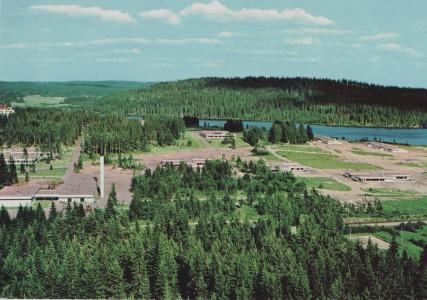 Tässä 1970-luvun alun kuvassa näkyvät jo useat Suojarinteen rakennukset: vasemmalla etualalla 1965 talousrakennus piippuineen poiskaivetun lammen edessä, sitten kolme apilarakennusta: Neliapila, Puna-apila (Ranta-apila) ja Valkoapila (Apila), jotka valmistuivat 1966. Mäellä on Harjula (Kotiharju), koivujen peittämä Rantakoti, jotka valmistuivat 1965 sekä Päivöla ja Tuulentupa 1967. Aivan vasemmassa yläreunassa pilkottaa 1968 valmistunut kerrostalo Savontien varressa. Tämän jälkeenkin piti rakentaa vielä neljä taloa, mutta avohoito alkoi jo vallata alaa ja rakennettiin vain koulu- ja terapiatalo (1969) rannan lähelle. Siksi Suojarinteellä on niin paljon nurmikenttää ! Kuvan otti ja painoi Mainos Varteva 1970 (MV n:o 348).