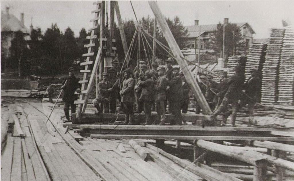 Postikorttikuvan suunnasta on otettu myös tämä kuva, mutta ilmeisesti joitakin vuosia aiemmin, sillä sillan pielessä juntataan paalua ja puut taustalla ovat aavistuksen pienempiä.  Luultavasti siltaa on kunnostettu 1906 ruoppauksessa ja 20-luvun koskensyventämisissä, mutta todennäköisempi homma tässä lienee sillan alta kulkevan uittorännin ohjainten junttaus. Kuva siis todennäköisesti 20-luvulta. Porukan lukkariksi on tunnistettu Eero Kuivakangas.