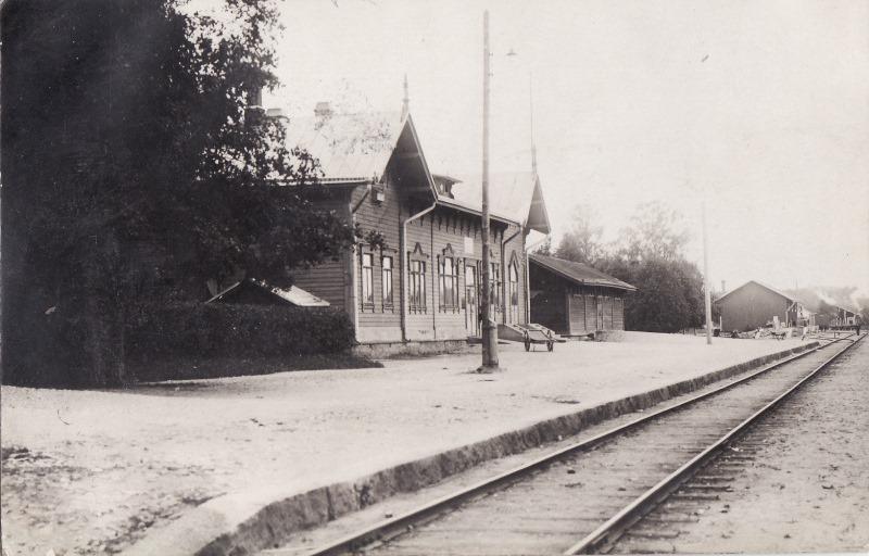 """Hiljainen Suolahden asema. Lastauskärryt jääneet odottamaan seuraavaa junaa. Jos 1902 halusi lähteä vaikka Sumiaisiin laivalla junan tultua asemalle, joutui odottamaan seuraavaan aamuun klo 5:een. Yleisön vaatimuksesta odotusaikaa lyhennettiin 1903, ja niin päästiin helpottavasti matkaan jo klo 2:lta yöllä. Tästä sai höyrylaivayhtiö paljon kehuja. Suomalainen-lehti kirjoitti kiittävästi """"Kaikessa tapauksessa on matkustusnopeus tyydyttäwä – ja nykyjan tarwetta wastaava"""". Uudistus tarkoitti, että jos Helsingistä lähti aamulla klo 7 , saattoi päästä Jyväskylään klo 16 aikaan ja siitä Suolahteen klo 18:ksi – ja edelleen Wiitasaari-laivaan sitten jo aamuyöllä klo 2. Kuva lienee 30-40-luvun vaihteesta, ja mielenkiinto kohdistuu suureen makasiiniin nykyisen muuntajan kohdalla."""