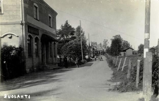 """Suolahden pääkatu 1930-luvulla. Kovin suurta ei liikenne ole. August kirjoittaa 11.5.1937 Nivalaan, että Suolahdessa on 35 astetta lämmintä ja Hannalle """"oikein hauskoja helluntaipyhiä """". Kortissa vasemmalla on Tampereen Osake-Pankin ns. Pörssitalo, jonka toisessa kulmassa on kahvila kyltteineen. Maidonhakureissulla oleva poika kivittää jotakin asiaa vanhan ukon katsellessa vieressä miten osuu. Maitokuljetus etenee Osuuskaupalle päin ilmeisen tuttua reittiä, sillä kuski kävelee vieressä ja hevonen vetää rauhallisesti kärryjä entisen Simo Niemen kaupan kohdalla. Eteenpänä Yhdyspankin pylväässä taitaa näkyä Ruotsin lippu, vaikka Ruotsin kansallispäivä on vasta 6. kesäkuuta. Ruotsissa tosin liputetaan Helluntainakin, joten olisiko Yhdyspankissa ollut joku ruotsinmielinen ? Seuraavana vuonna pankki muutti Äänekosken Viiskulmaan ja tilalle tuli Suolahden kauppalantoimisto (vrt. Ramin kortit 45)."""
