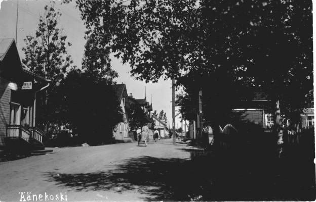 Tältä näytti Äänekosken Kauppakatu vielä 1930-luvun alussa. OIkealla koivujen ja aidan takana Ilmari Honkosen omistama liiketalo, jonka paikalla nyt Yhdyspankin talo. Puiden kohdalla liikennevalot. Vasemmalla Kummun ja Härkösen kahvilat, jonka jälkeen Osuuskaupan talo ja kahvila, jolla kohdalla tätä nykyä sulanut luistinrata. Kuvaaja itse on vanhan Viiskulman yläreunalla. Valokuvakortti ei ole aivan harvinainen, joten sitä vielä löytynee kotialbumeita myöten.