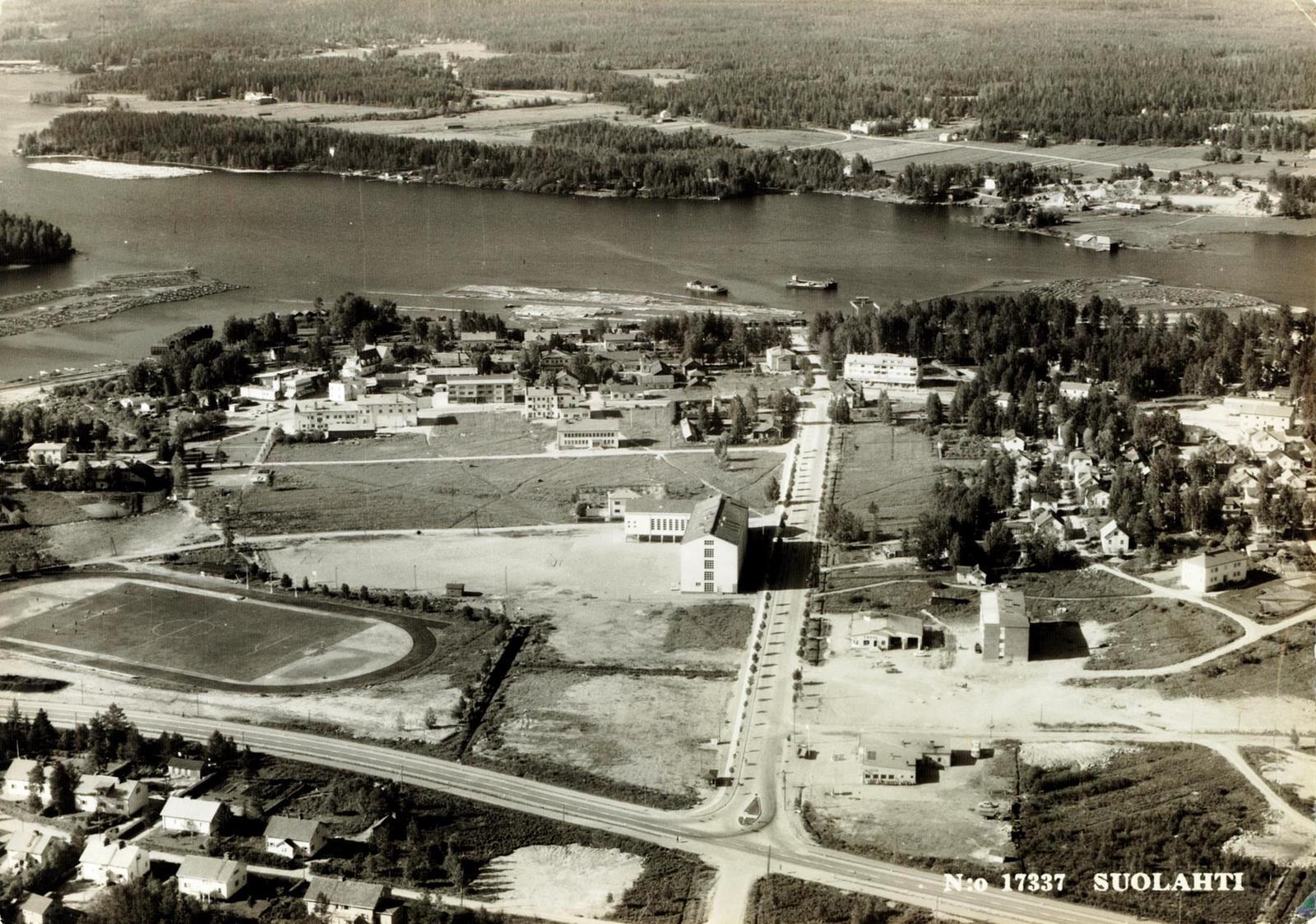 """Koulukadun ja Hopeapajunkadun (Puistokadun) kerrostaloalue on tunnusomainen Suolahdelle. Näissä kahdessa ensimmäisessä kuvassa alue on pelkkää peltoa. Tämä kuva on vuodelta 1964 ja Lastaajankadun ensimmäinen kerrostalo on miltei valmis huoltoaseman vieressä. Kaksi huoltoasemaa täällä """"laitakylällä"""" kertovat jo autoistumisen alkaneen. Ostokeskus (1967) ei ole vielä parkkipaikkoineen muotia tukemassa."""