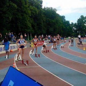 Aino Pulkkinen Suomen lippu rinnassa 200 metrin lähtöviivalla ulommaisella radalla.