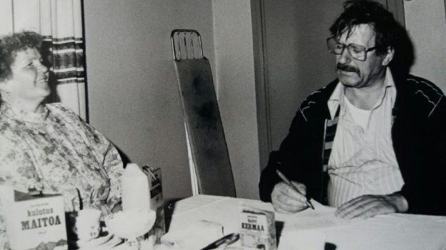 Ihmisyyden tunnustajien perustaja Martta Horjander ja Mikko Niskanen kirjoittavat vuokrasopimusta heinäkuussa 1981. Kuva otettu Kaavilla, yhteisön silloisessa asuinpaikassa Ahosenniemessä.