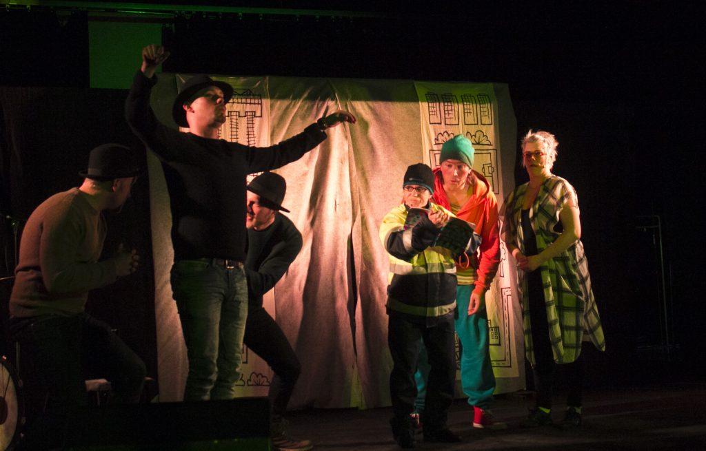 Maurin vanhemmat selittävät havainnevihkon (jota esittivät E4-bändin pojat) avulla pojalle sademetsien tuhoamisen.