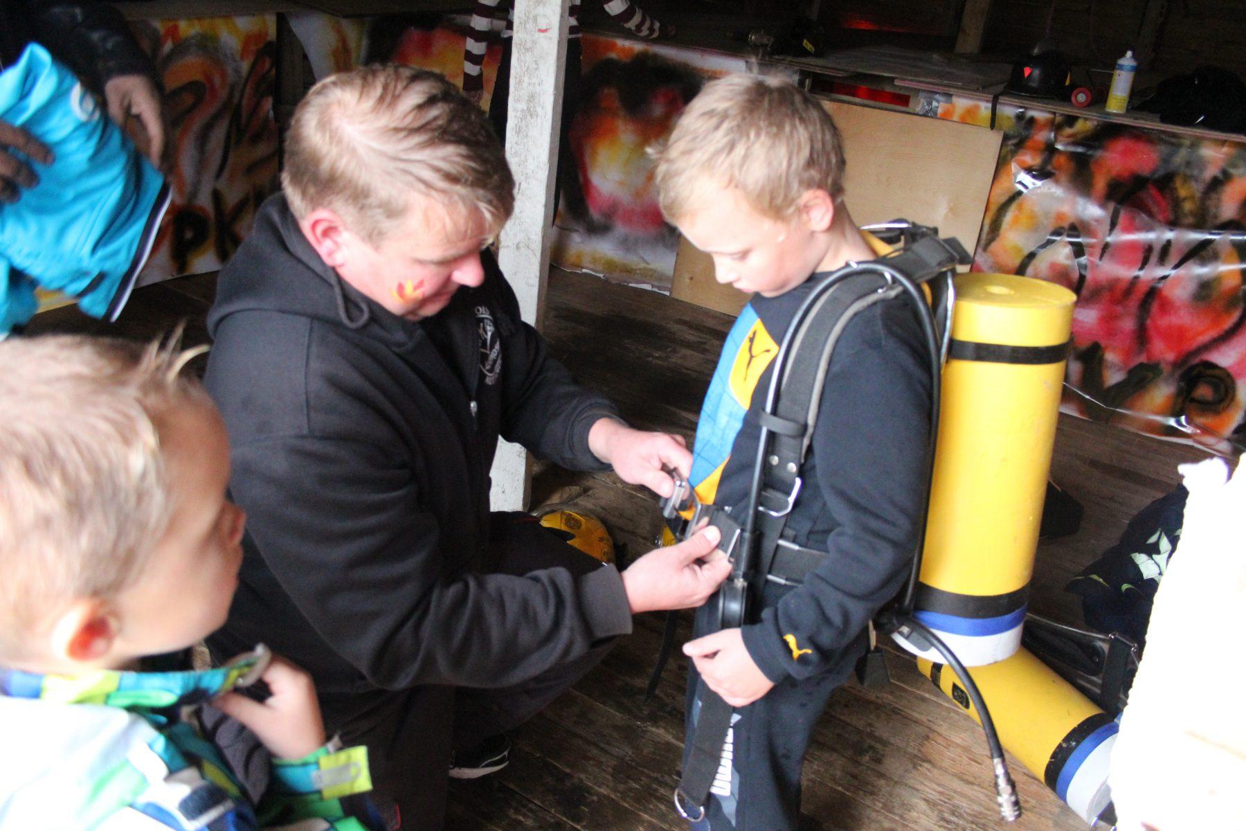 Timo Pulli kiinnittää tulevan palomiehen selkään happipulloa, jota tarvitaan savusukellusradalla.